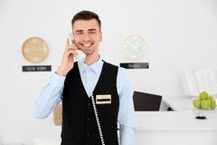 Male receptionist talking on phone. At workplace in hotel Stock Photos