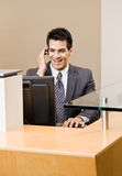 Male receptionist talking on telephone earpiece. Working at front desk Royalty Free Stock Photography