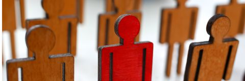 Male red plastic toy businessman silhouette. Wooden crowd figure background closeup. Manipulate work recruitment transfer labour inspectorate experience royalty free stock image