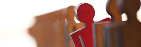 Male red plastic toy businessman silhouette. Wooden figure background closeup. Manipulate work recruitment transfer labour inspectorate experience exchange man stock image