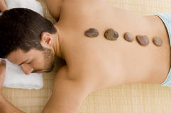 Male relaxing for hot stone treatment Stock Photography
