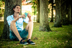 Male relaxing under tree outdoors Stock Photos