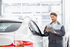 Male repair worker using tablet PC while standing by car in workshop Stock Photo