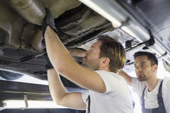 Male repair workers examining car in workshop Royalty Free Stock Images