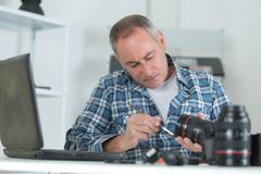 Male repairing camera at workplace. Male repairing a camera at his workplace Stock Images