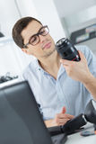 Male repairing camera at workplace Stock Image