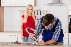 Male Repairman Installing Faucet Of Kitchen Sink. Young Male Repairman Installing Faucet Of Kitchen Sink With Woman Standing In Kitchen Room stock images