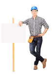 Male repairman leaning on a blank banner Royalty Free Stock Images