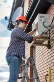 Male repairman standing on top of stepladder and fixing air conditioner. Repairman standing on top of stepladder and fixing air conditioner Royalty Free Stock Photo
