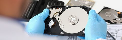 Male repairman wearing blue gloves is holding a hard drive. A male repairman wearing blue gloves is holding a hard drive from computer or laptop in hands Stock Photography