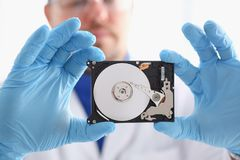 Male repairman wearing blue gloves is holding a hard drive Stock Image