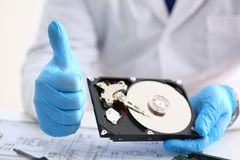 Male repairman wearing blue gloves is holding hard drive. From computer laptop in hands show OK thumbs up. Performs diagnostics performs urgent repairs recovery Stock Photography