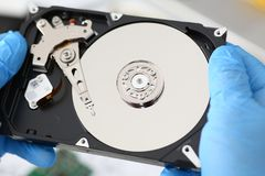 Male repairman wearing blue gloves is holding a hard drive. A male repairman wearing blue gloves is holding a hard drive from a computer or laptop in his hands Stock Photography