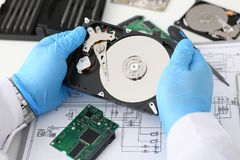 Male repairman wearing blue gloves is holding a hard drive Royalty Free Stock Image