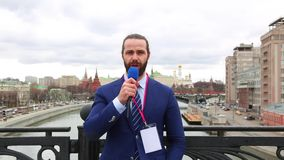 Male reporter with a microphone tells news camera on the background of the city.