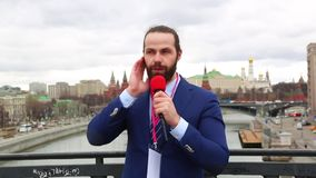 Male reporter with a microphone tells news camera on the background of the city. Russia, Moscow