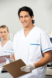 Male Researcher Holding Clipboard In Lab. Portrait of young male researcher holding clipboard with colleague in background Royalty Free Stock Photos