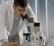 Male researcher looking through a microscope in a. Scientist using a microscope, chemistry related or medical design Royalty Free Stock Photos