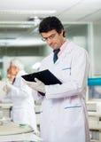 Male Researcher Reading Clipboard Stock Photo