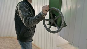 A male researcher rotates the manual wheel of the opening mechanism of the dome doors of a solar observatory. Scientific stock video footage
