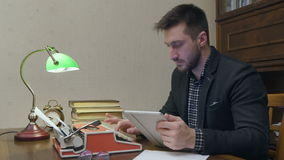 Male researcher using digital tablet and typing on typewriter at his study desk stock video footage
