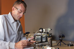 Male Researcher Wearing Safety Glasses. A researcher in a lab coat studying a piece of equipment for an experiment. He is wearing safety glasses. Horizontal shot Stock Image