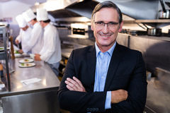 Male restaurant manager standing with arms crossed. In commercial kitchen Stock Images