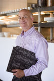 Male restaurant manager standing in commercial kitchen, carrying menus, smiling, side view, portrait Stock Images