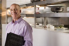 Male restaurant manager standing in commercial kitchen, carrying menus, smiling, side view, portrait Stock Photos