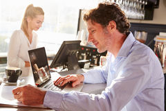 Male restaurant manager working on laptop Stock Images