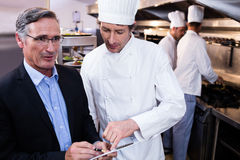 Male restaurant manager writing on clipboard while interacting to head chef Royalty Free Stock Photos