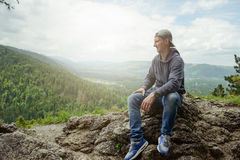 Male resting and enjoying the mountain sitting on rock Stock Photo