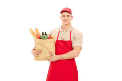 Male retail worker holding a grocery bag. Isolated on white background royalty free stock photography