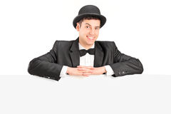 A male with retro hat and bow tie posing behind a blank panel Royalty Free Stock Image