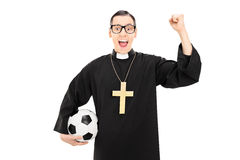 Male reverend holding football and raising a fist Royalty Free Stock Photos