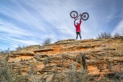 male rider lifting his fat bike on a sandstone cliff Royalty Free Stock Photography