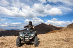 Male rider sitting on ATV at mountain Royalty Free Stock Images