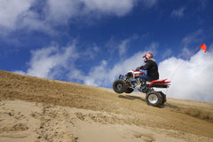 Male riding ATV up sand dune hill Stock Image