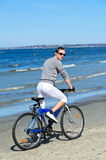 Male riding a bicycle by the sea Stock Image