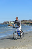 Male riding a bicycle by the sea Royalty Free Stock Images