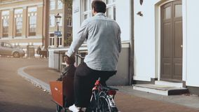 Male riding a cargo bicycle with two kids. Slow motion back view. Family happy bike ride. Single dad. Single parent. Adult male riding a cargo bicycle with two stock footage