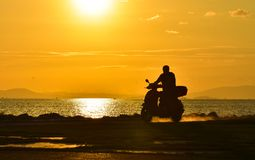 Male riding motorcycle over sunset Royalty Free Stock Image
