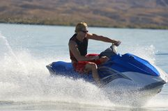 Male Riding PWC. Young men riding personal watercraft on lake Stock Image