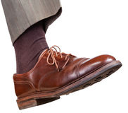 Male right foot in brown shoe takes a step Stock Photos