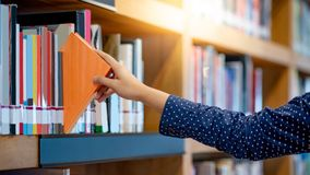 Male hand picking book in library. Male right hand choosing and picking orange book in public library. Pulling off selected textbook. Education research and self Stock Image