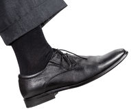 Male right leg in black shoe takes a step Royalty Free Stock Photo