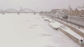 Male on the riverside copter pan over the winter riverside near a town 1080p 25 fps stock footage