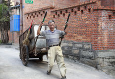 Male road cleaner pull garbage dray Stock Photos
