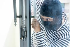 Male robber/Burglarize try to break into the room to steal. Criminal concept Royalty Free Stock Photo