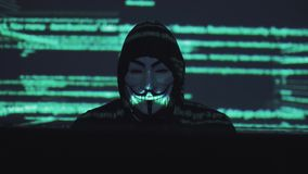 A male robber in a mask works on a computer in a dark room. computer code is reflected on his face. the hacker breaks